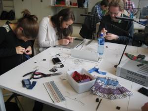 Konsentrerte studenter. Tekstiler og elektronikk i herlig blanding på bordet.